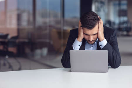 Feeling exhausted. Frustrated young beard man keeping eyes closed while sitting at his working place in office