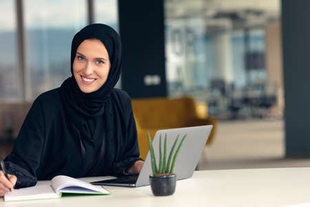 professional young muslim business woman using mobile digital tablet computer at work