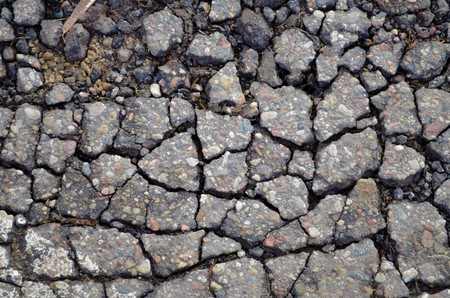 Old asphalt road with many dangerous cracks  Stock Photo