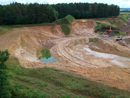 Aerial view on open pit mine of sand and hummus, flooded with water. Standard-Bild