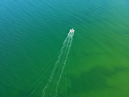 Aerial view on small fishing boat sailing straight at sea waters