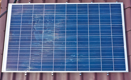 Aerial view on house roof covered with solar panels producing electric energy. Photovoltaic technology. 免版税图像