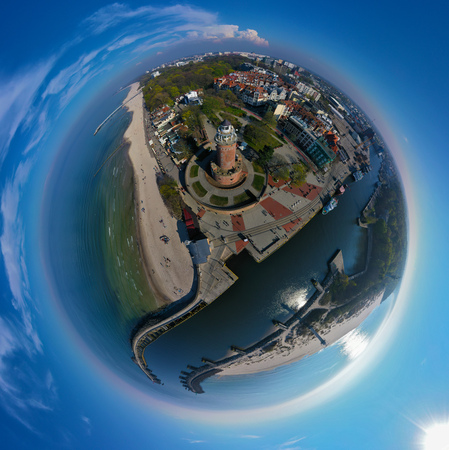 Aerial 360 panoramic tiny planet view on brick brown lighthouse at baltic sea shore with tourists and ship port entrance