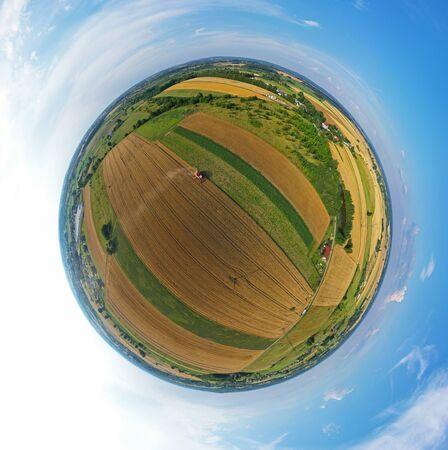 Aerial drone 360 degree spherical tiny planet view on red harvester during wheat field harvesting, collecting seeds, making dust cloud, driving forward.