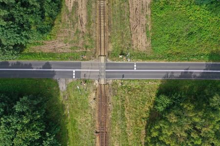 Aerial drone top down view on railroad crossing with asphalt road in the forest