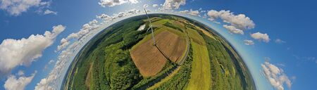 Aerial drone 180 degree arch view on wind turbine, snake shape road, wheat fields and forest during summer