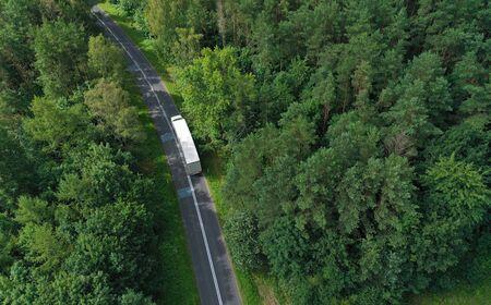 Luftdrohnen-Perspektivansicht auf weißem LKW mit Frachtanhänger, der auf einer kurvigen Asphaltstraße durch den Wald fährt.