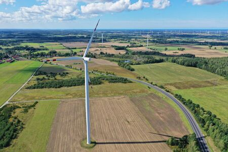 Aerial drone perspective view on wind turbine, snake shape road, wheat fields and forest during summer