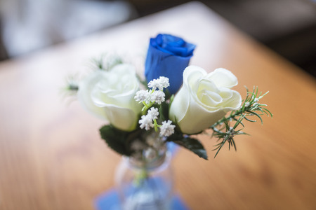 Close up of blue and white roses as a table decoration in a small glass vase at a traditional English wedding