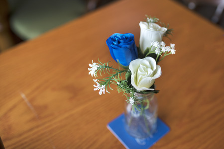 Close up of blue and white artificial roses as a table decoration in a small glass vase at a traditional English wedding Stock Photo
