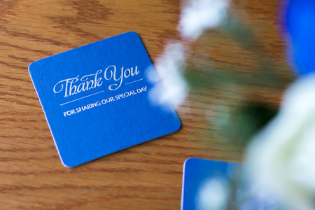 Blauwe feestbiermat met zilveren tekst op een houten tafel bij de receptie van een hernieuwing van geloften met de vermelding â ? ~Dank je wel voor het delen van onze speciale dagâ ? ? Stockfoto