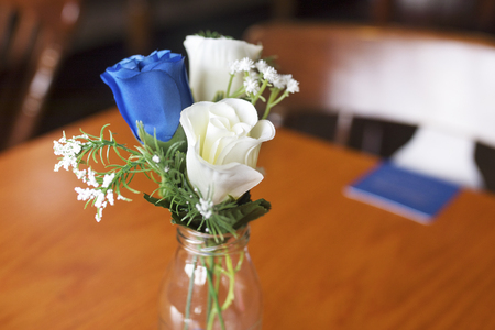 Close up of atrificial blue and white roses as a table decoration in a small glass vase at a traditional English wedding in the UK