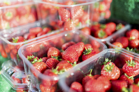 Close up of fresh and ripe English summer strawberries in punnets on a market stall in the Yorksire in the UK