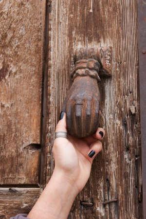 Woman hand knocking vintage door photo