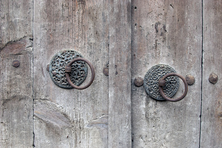 ancient wooden gate with two door knocker rings close-up 스톡 콘텐츠