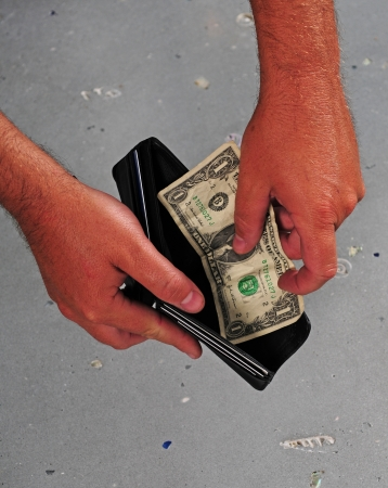 empty wallet: Man spending last dollar while being left with an empty wallet