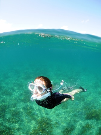 Young woman snorkeling underwater in the clear blue ocean Stock Photo - 13774473