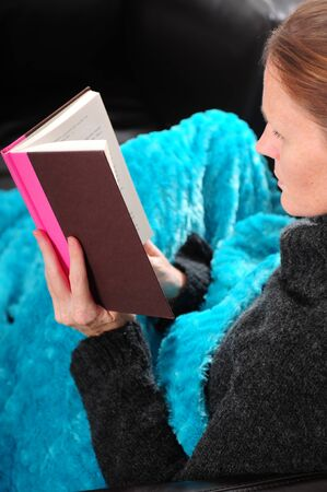 A woman with red hair cuddling up with a book under a blanket for a relaxing day photo