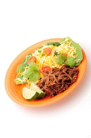 ropa vieja, una comida cubana, en una placa de color naranja con una ensalada saludable sobre un fondo blanco