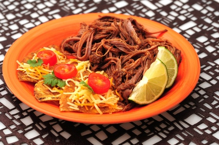 Spicy shredded beef with cheesy nachos on an orange plate with a geometric background photo
