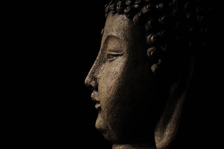 Profile of Buddha head on a black background with room for text