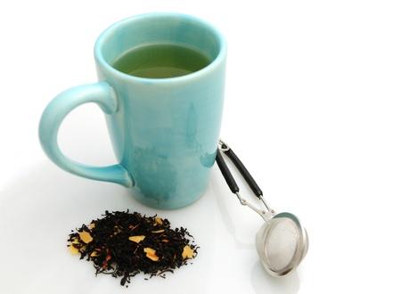 tea strainer: Hot cup of black tea with tea leaves and tea infuser