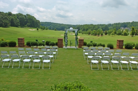 A view of a wedding setup with chairs and floral arch before wedding photo