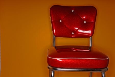 A red vinyl vintage chair on an orange background