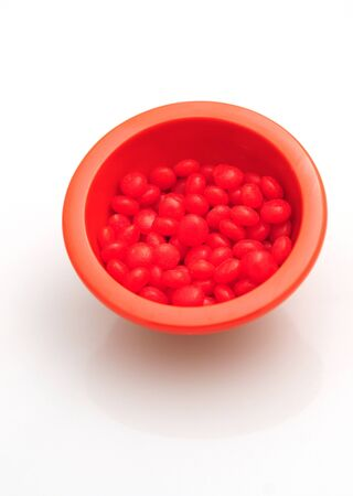 hots: red hots candy in a bowl isolated on a white background Stock Photo