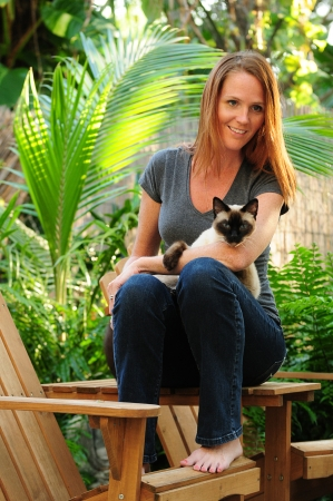 Pretty young woman with red hair holding a Siamese cat while sitting on wooden chairs in warm summer weather photo