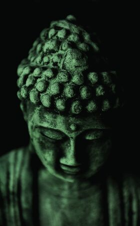 Buddha statue on black background with green