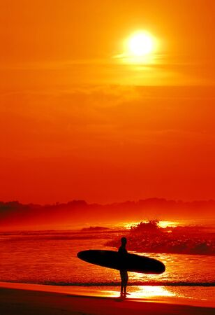 Surfer with sunset background in Costa Rica Stock Photo