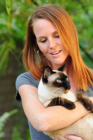 Pretty young redhead woman holding Siamese cat with blue eyes whild standing outdoors photo