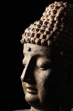 eastern philosophy: Buddha head isolated on black background Stock Photo