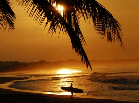 Costa Rica sunset with surfer admiring the waves 스톡 콘텐츠