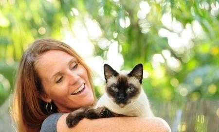 Mooie vrouw met rood haar deelneming Siamese kat buiten