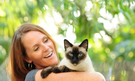 Pretty woman with red hair holding Siamese cat outdoors photo