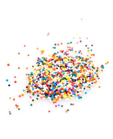 Candy sprinkles in all the colors of the rainbow isolated on white photo