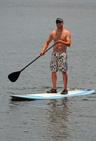 board shorts: A young man in board shorts and a visor on a paddleboard while exercising