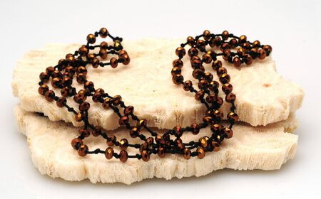 A beautiful long, beaded brown necklace on coral Imagens