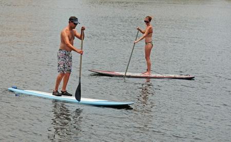 joven y paddleboarding mujer joven en el oc�ano