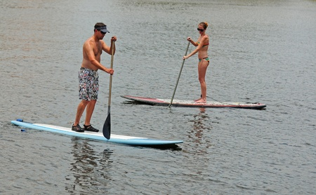 young man and woman couple paddleboarding in ocean photo