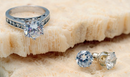 engagement ring: Beautiful diamond engagement ring and diamond stud earrings on coarl