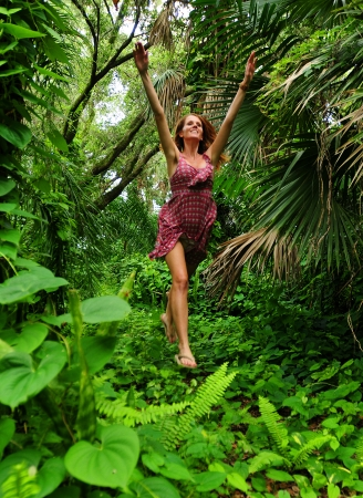 Beautiful young woman jumping for joy in forest photo