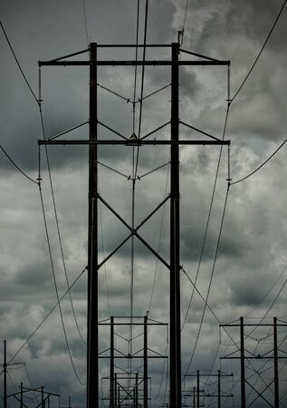Group of Power lines with dark stormy sky in the background