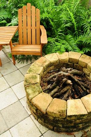 Adirondack stoel en vuurkorf in een ontspannen achtertuin Stockfoto