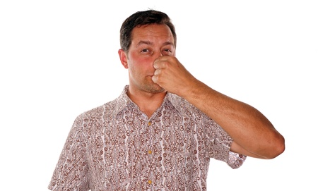plugging: Man plugging nose after smelling something with a foul odor