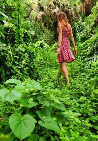 Young woman wearing flower dress walking through lush rainforest photo