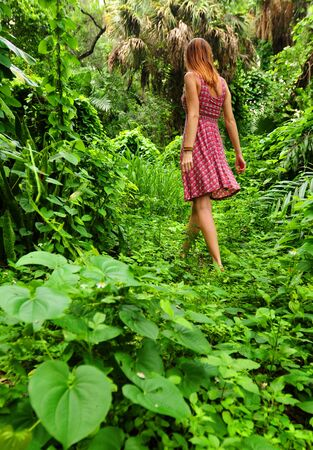 Young woman wearing flower dress walking through lush rainforest photo