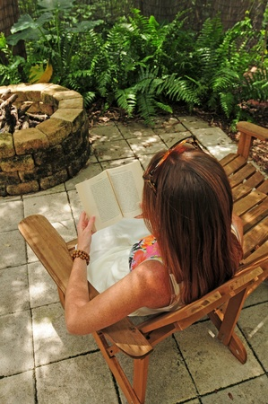 fire pit: Young woman reading book in Adirondack chairs outdoors